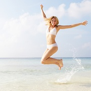 Happy Woman Jumping On The Beach - The Pill and Period Delay - Picture