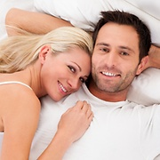 Man and woman looking satisfied in bed